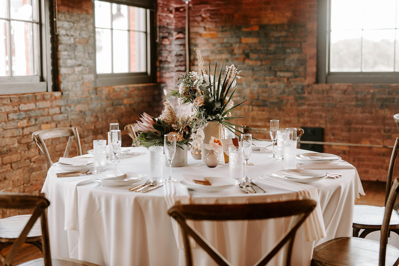 Boho Whimsical Wedding Reception Decor, Round Table with White Linen, Wooden Crossback Chairs, White Vases with Palm Fronds, King Protea, Blush Pink and White Floral Centerpieces   Tampa Bay Wedding Planner Coastal Coordinating