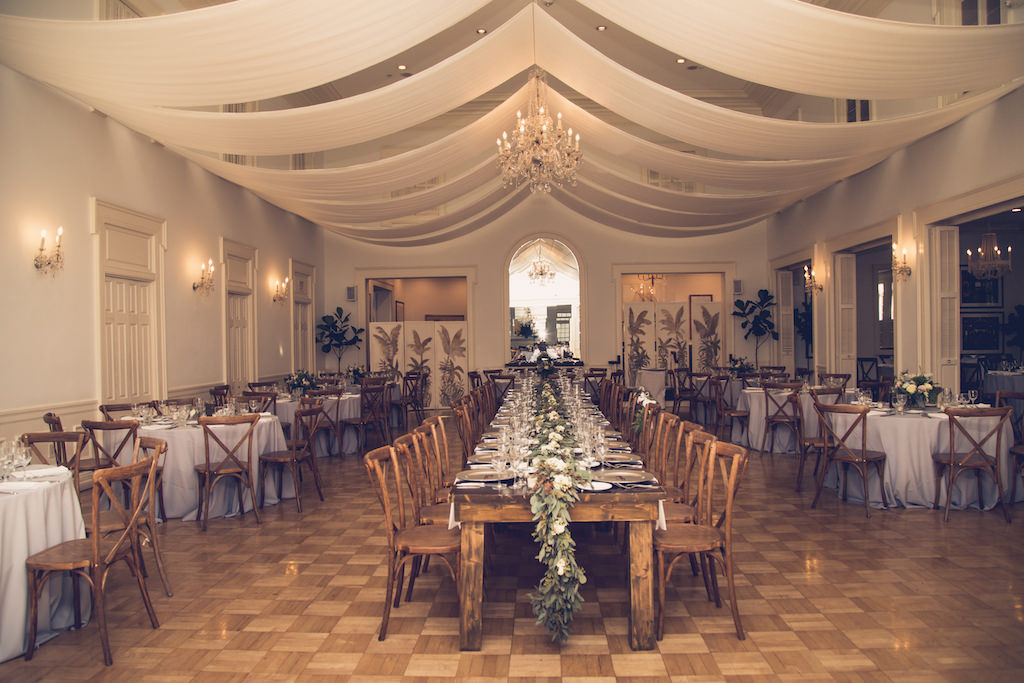 Rustic Chic Inspired Wedding Reception Decor Boho Elegant Inspired Greenery Long Wooden Feasting Tables Green Eucalyptus Leave Garland Table Runner Wood Cross Back Chairs White Ceiling Draping And Crystal Chandelier Florida Luxury