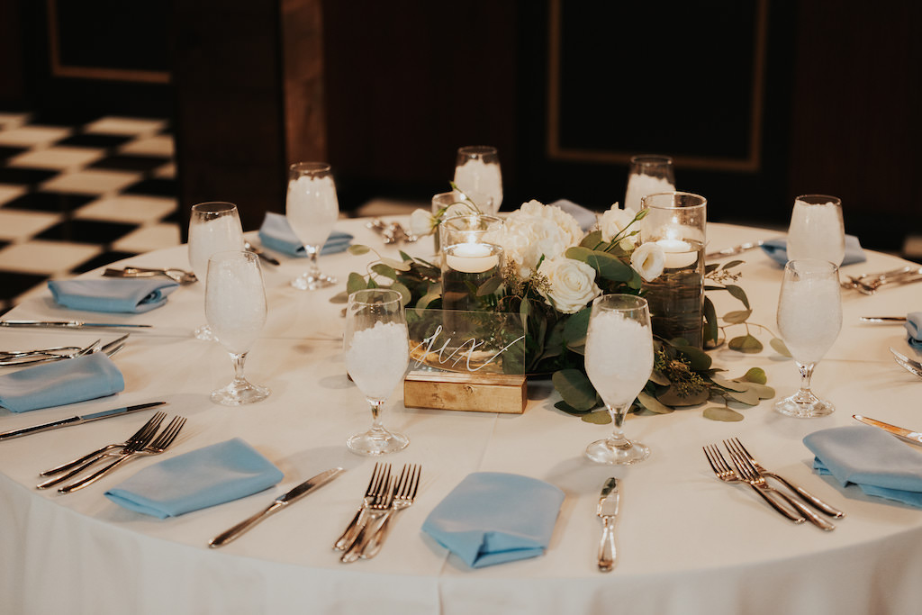 Elegant Wedding Reception Decor Round Table With White Tablecloth Dusty Blue Linen Napkins Acrylic Clear And Gold Table Number White Roses And Eucalyptus Floral Centerpiece Hurricane Glass Cylinder With Floating Candles