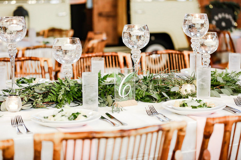 Industrial Boho Chic Wedding Reception Decor, White Linens, Bamboo Wooden Chairs, Greenery Garland Table Runner, Tall Glass Candlesticks, Clear Acrylic Table Number Sign | Tampa Bay Wedding Photographer Lifelong Photography Studio | Wedding Planner Special Moments Event Planning | Wedding Tables, Chairs, Linen Rentals Gabro Event Services
