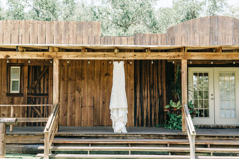 Romantic Lace Wedding Dress Hanging from Antique Wood Porch | Tampa Bay Private Outdoor Wedding Venue Florida Rustic Barn Weddings