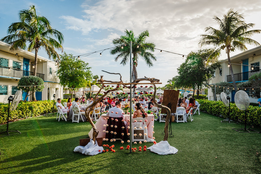 Tropical Wedding Reception Portrait and Decor, Birchwood with Hanging Blush Pink, Orange and Red Carnation Flowers | St. Petersburg Wedding Venue Postcard Inn on the Beach