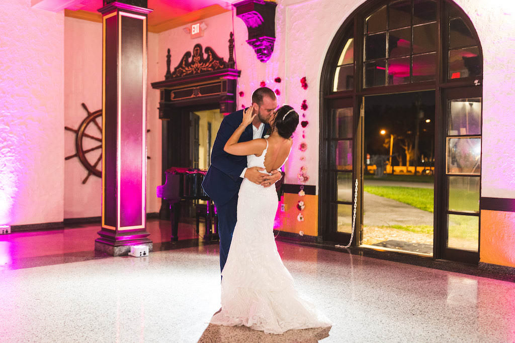 Romantic Bride and Groom First Dance Kiss Wedding Portrait with Pink Uplighting | Tampa Bay Wedding DJ Grant Hemond & Associates | St. Petersburg Wedding Reception Venue Admiral Farragut Academy