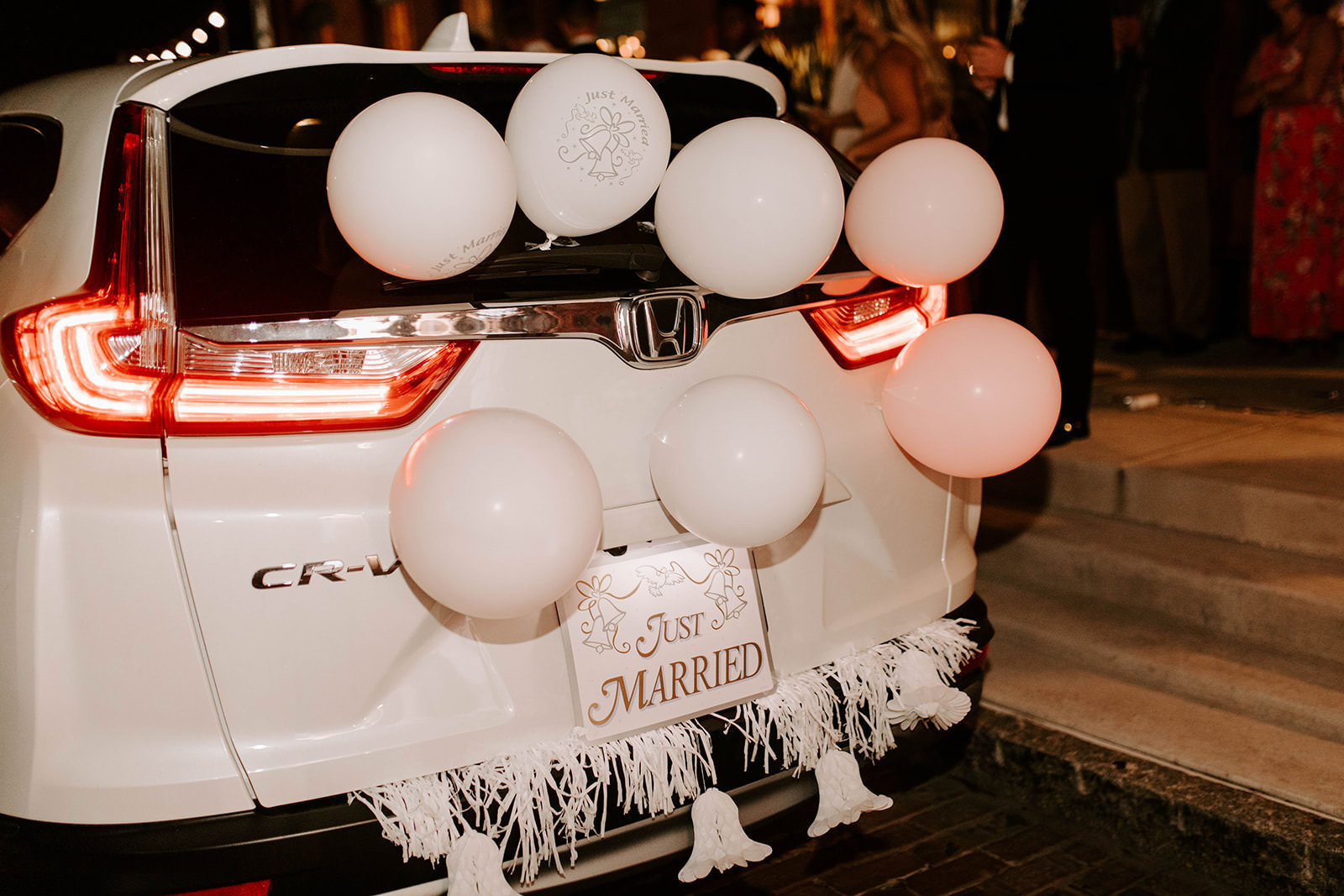 White SUV Decorated with White and Blush Pink Balloons and Just Married Sign Wedding Exit Car