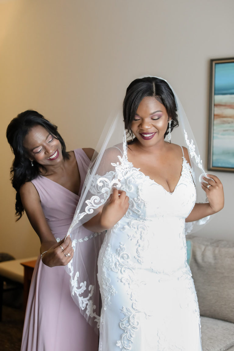 Bride Getting Ready Wedding Portrait in Fitted Lace V Neck Off the Shoulders Wedding Dress and Classic Veil with Bridesmaids in Mauve Dress | Tampa Wedding Photographer Lifelong Photography Studio | Wedding Hair and Makeup Michele Renee the Studio | Wedding Dress Boutique Truly Forever Bridal
