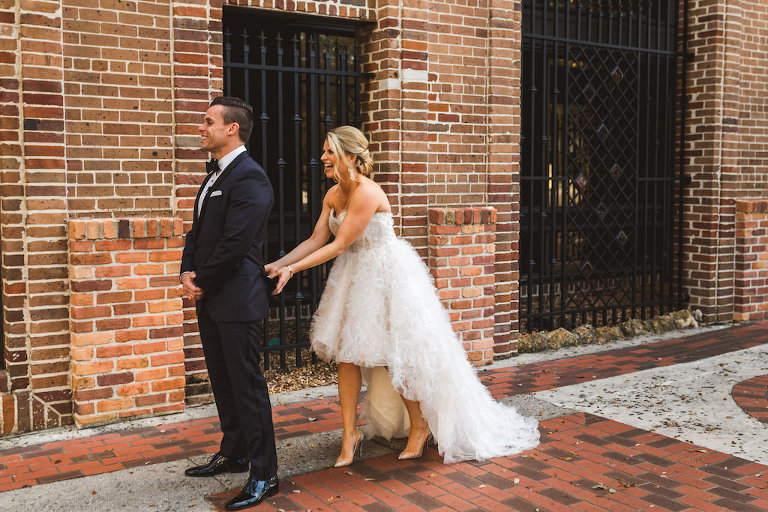 Tampa Bay Bride in Modern Ines Di Santo Ruffle High Low Ballgown Skirt Strapless Wedding Dress | Fun Silly First Look Wedding Portrait with Groom in Black Tuxedo | Wedding Dress Shop Isabel O'Neil Bridal Collection