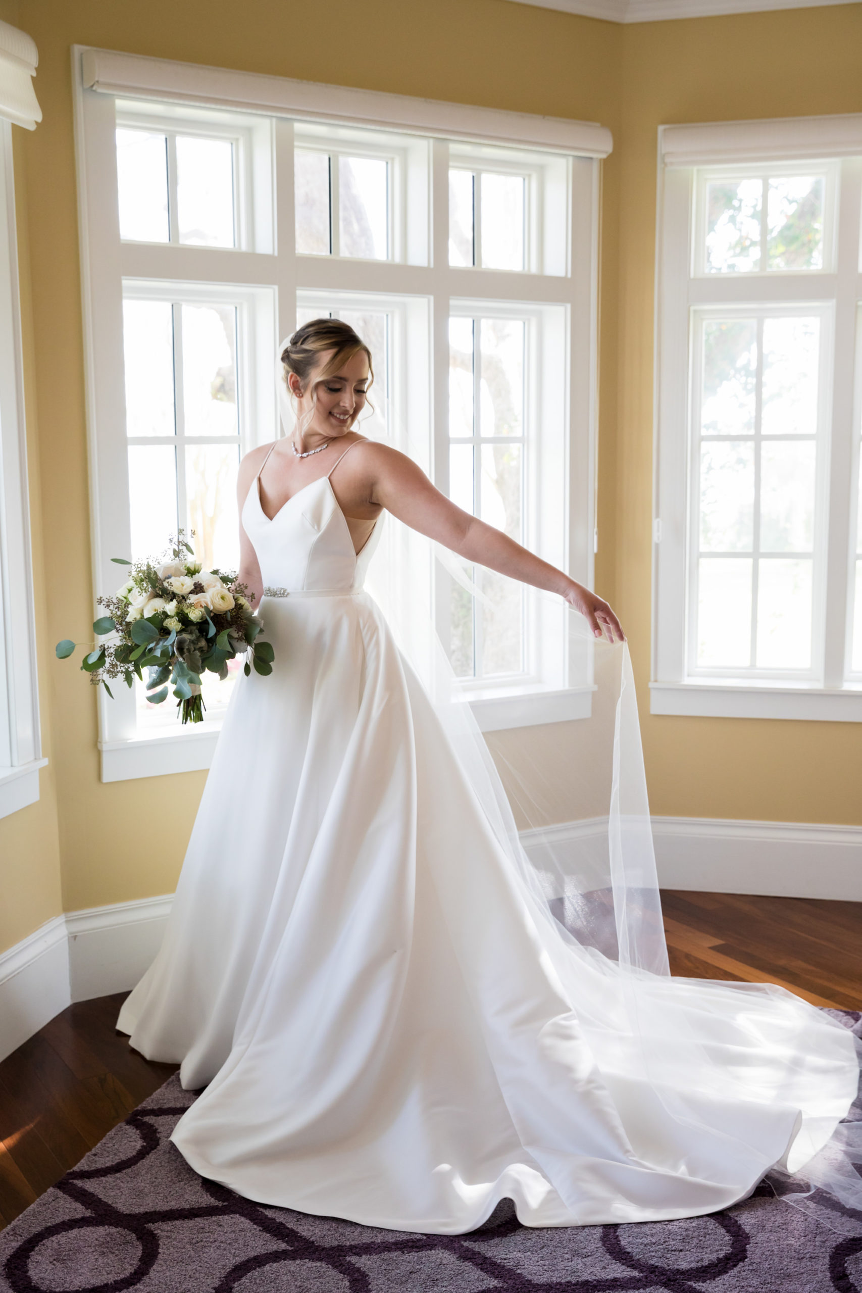 Tampa Bay Bride Beauty Portrait Wearing Justin Alexander A-Line V Neck with Straps and Rhinestone Belt Wedding Dress and Full Length Veil with Eucalyptus and Ivory Floral Bridal Bouquet