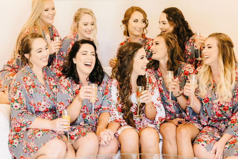 Florida Bride and Bridesmaids in Matching Gray and Blush Pink Floral Silk Robes, Bridal Party Drinking Mimosas Getting Wedding Ready Portrait