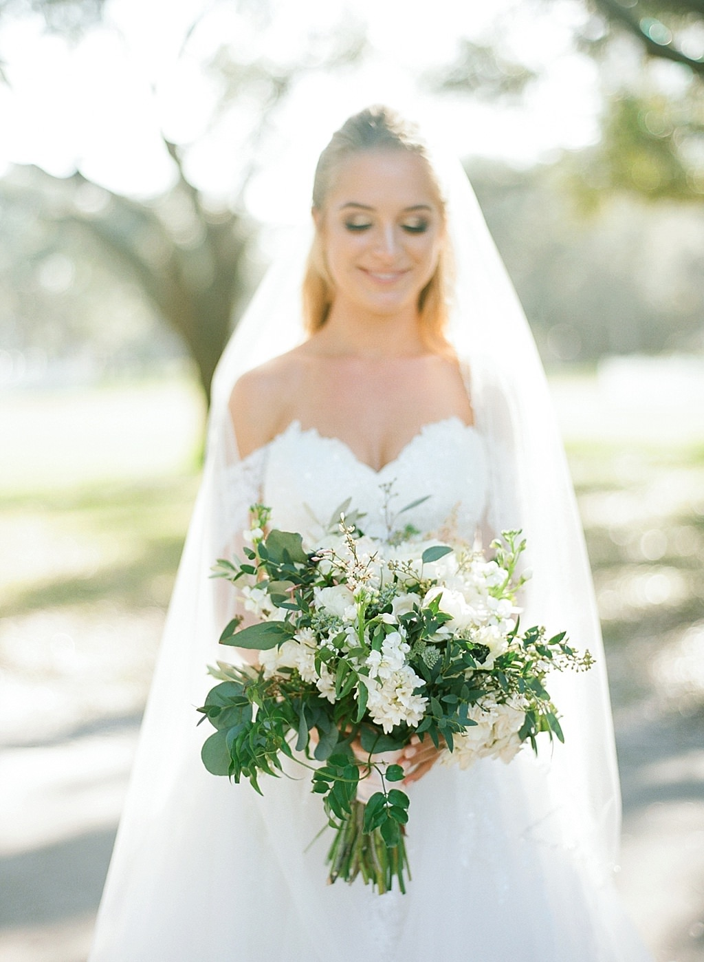 Elegant St. Pete Bride Beauty Wedding Portrait in Sweetheart Off the Shoulder Lace Ballgown Wedding Dress Holding Garden Inspired White Roses, Eucalyptus and Greenery Floral Bridal Bouquet