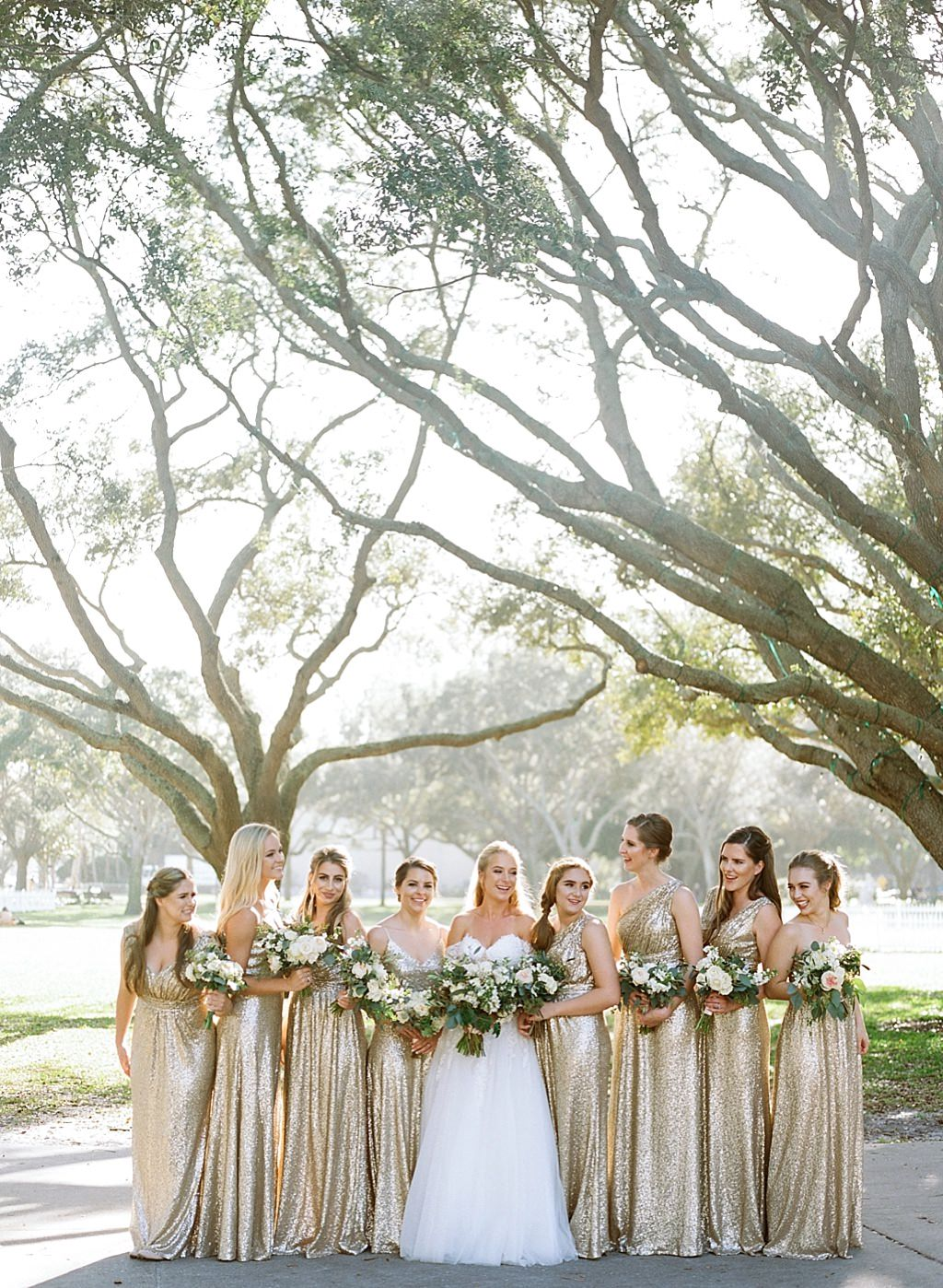 Outdoor Elegant Bride in Ballgown Wedding Dress and Bridesmaids in Randy Fenoli Matching Gold Sequin Dresses with Garden Inspired Floral Bouquets Bridal Party Portrait