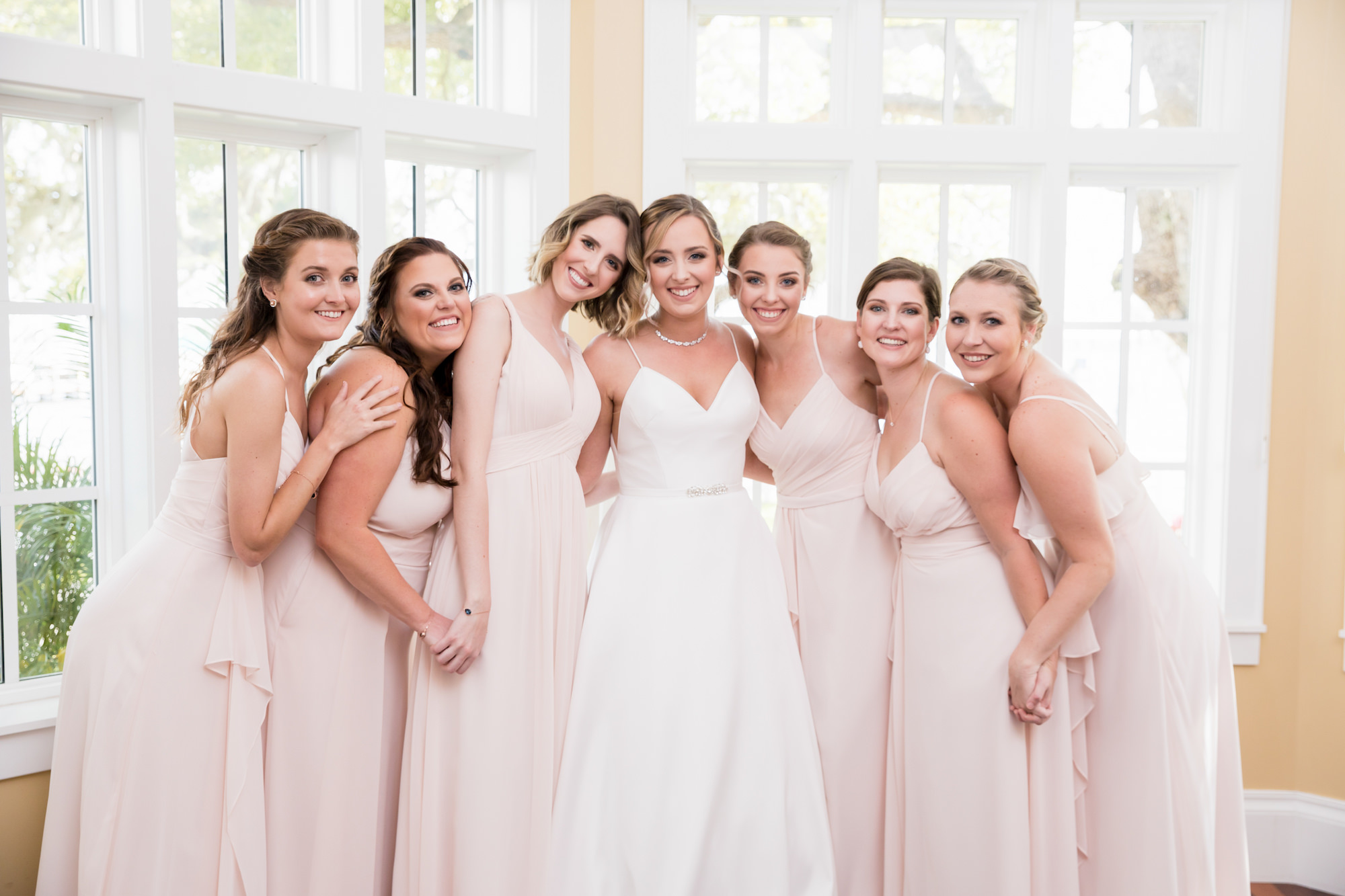Tampa Bay Bride Wearing V Neck A-Line with Straps and Rhinestone Belt Justin Alexander Wedding Dress, Bridesmaids in Blush Pink Mix and Match Dresses
