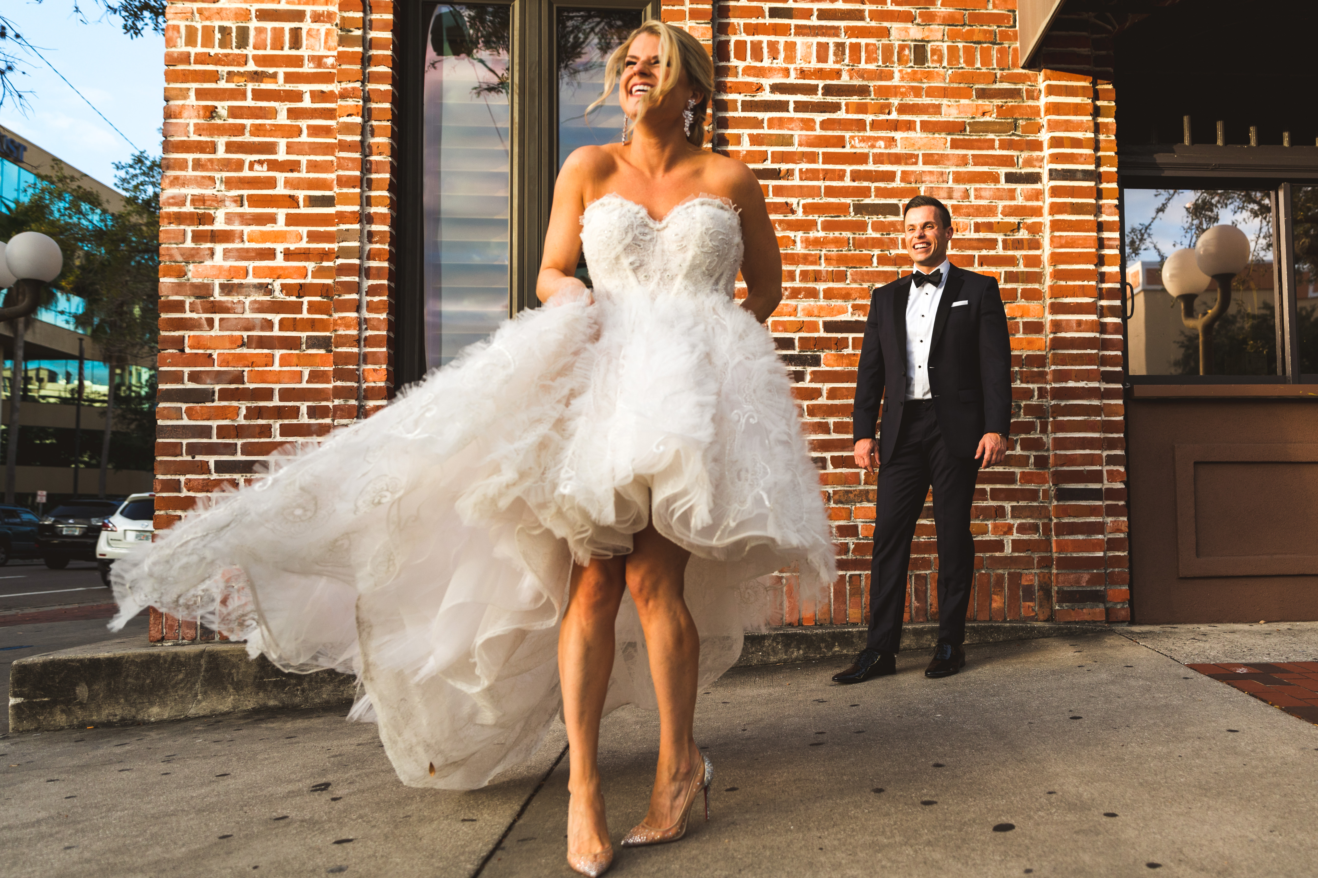 INSTAGRAM Fun Bride and Groom Outdoor St. Pete Wedding Portrait, Bride in Ruffle High Low Wedding Skirt and Strapless Dress, Clear Pointed Toe Wedding Shoes, Groom in Black Tuxedo   Wedding Dress Shop Isabel O'Neil Bridal Collection