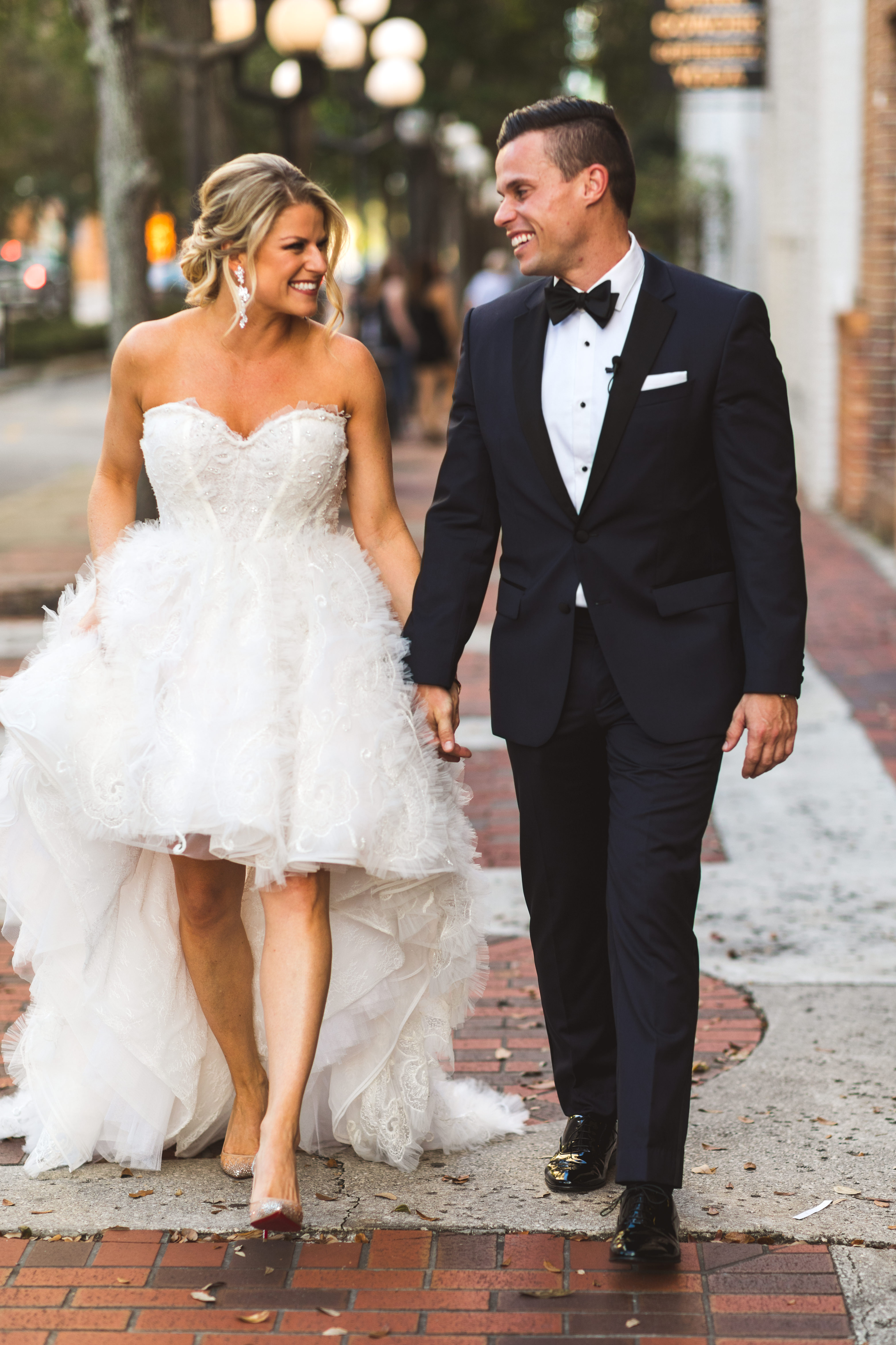 Modern Bride and Groom Holding Hands Wedding Portrait, Bride in Ruffle High Low Skirt Strapless Sweetheart Wedding Dress, Groom in Black Tuxedo   Ines DiSanto Wedding Dress Isabel O'Neil Bridal Collection