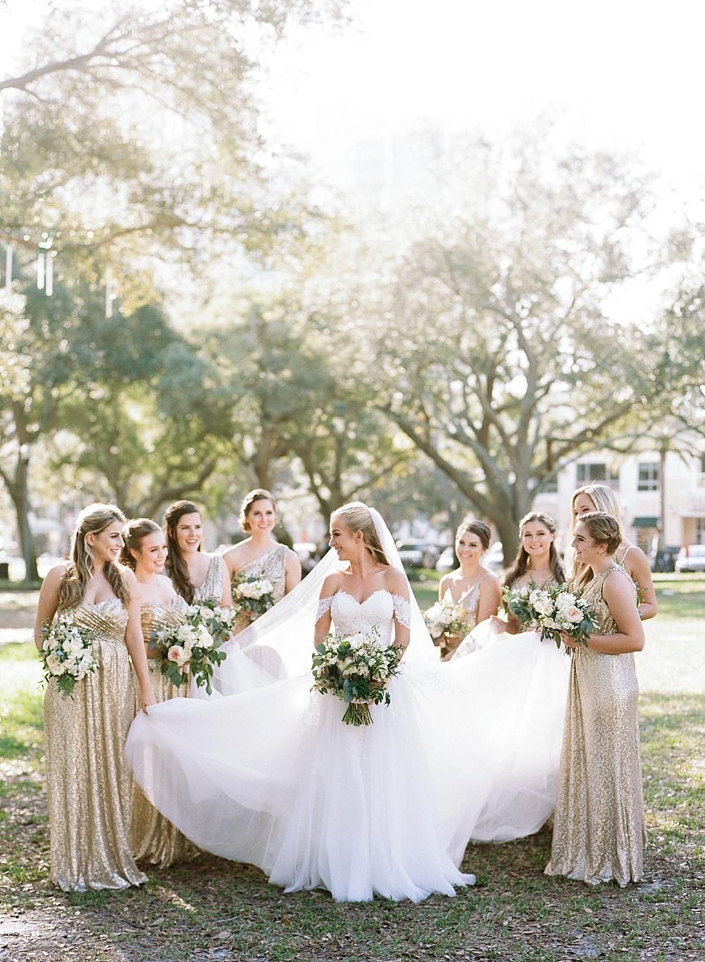 St. Pete Bride in Romantic Sweetheart Off the Shoulder Ballgown Wedding Dress, Bridesmaids in Randy Fenoli Sequin Gold Matching Dresses Holding Brides Dress Fun Wedding Portrait
