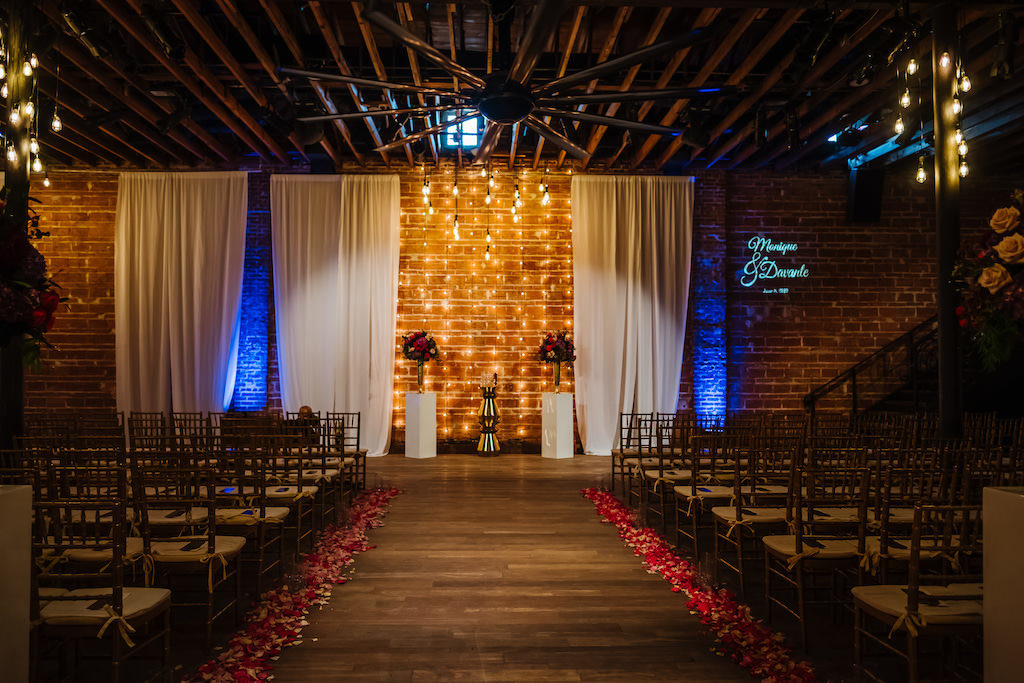 Romantic Garden Indoor Wedding Decor, Exposed Red Brick Wall Ceremony Backdrop with Vintage Hanging Lights, White Draping, Gold Chiavari Chairs, Blush Pink, Burgundy, Plum, Quartz and Magenta Florals, Flower Petals Lining Aisle | Historic Downtown St. Pete Industrial Wedding Venue NOVA 535