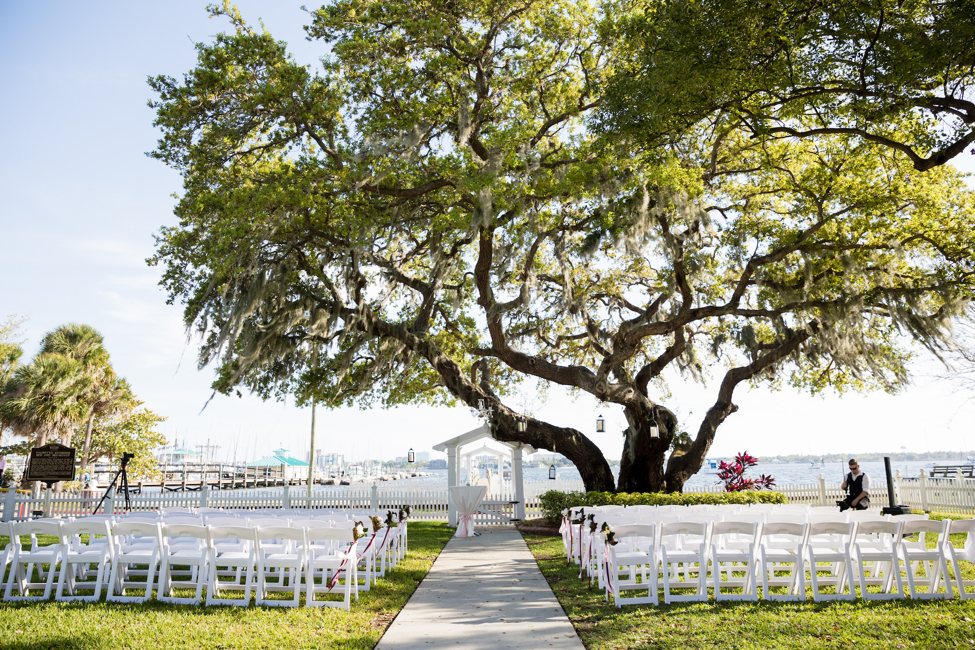 Simple Waterfront Wedding Ceremony Decor, White Folding Chairs and White Altar with Large Oak Tree and Lanterns   Tampa Wedding Venue Palmetto Riverside Bed and Breakfast   Sarasota Wedding Planner Coastal Coordinating