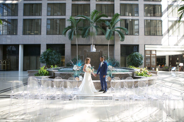 Unique Tropical Wedding Ceremony Decor, Acrylic Ghost Chair Seating, Bride and Groom Standing in Front of Fountain with Palm Tree Leave Arrangements | Tampa Wedding Chair Rentals Gabro Event Services | Wedding Planner and Florist John Campbell Weddings | Wedding Photographer Carrie Wildes Photography | Tampa Wedding Venue Centre Club
