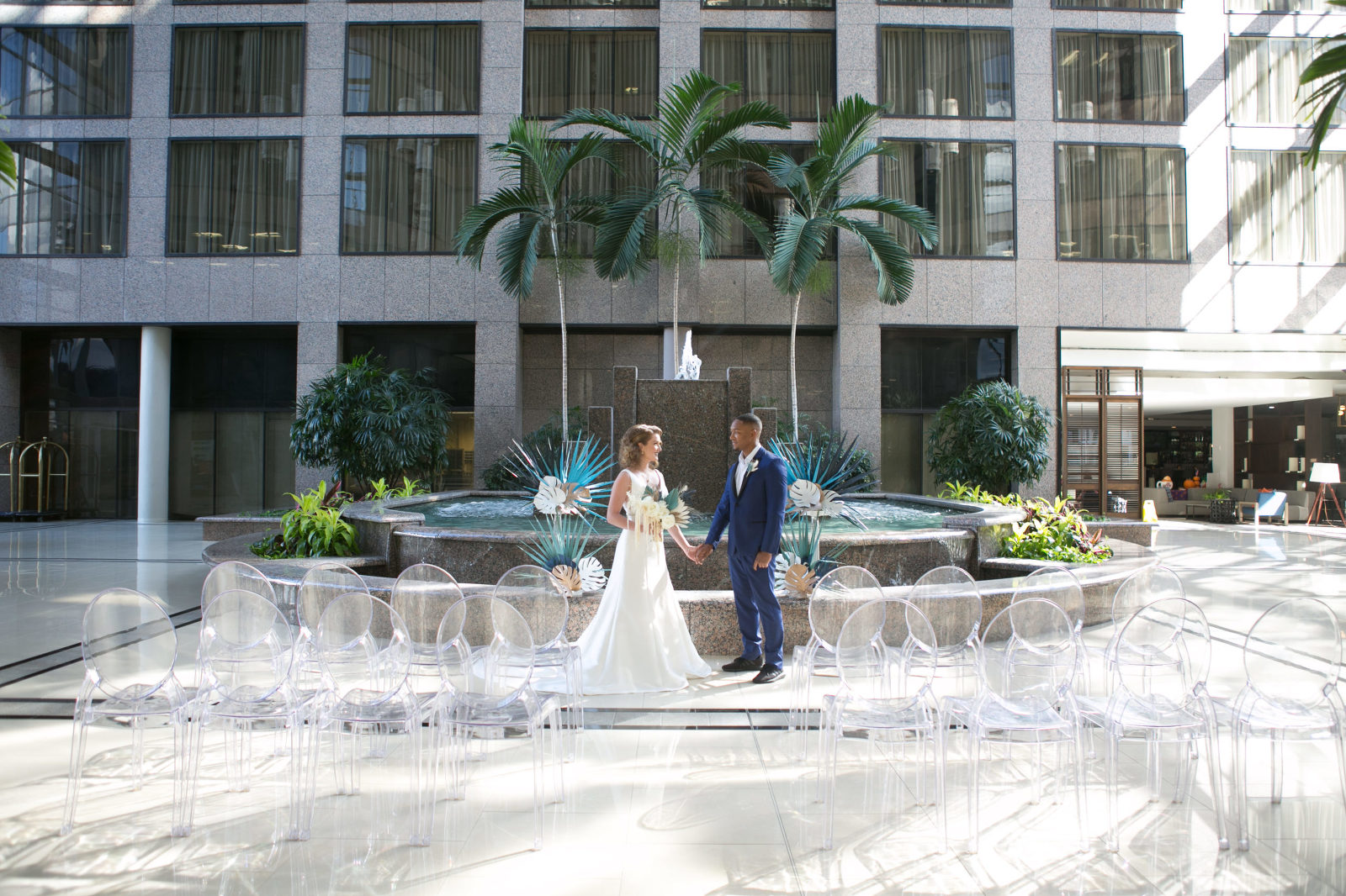 Unique Tropical Wedding Ceremony Decor, Acrylic Ghost Chair Seating, Bride and Groom Standing in Front of Fountain with Palm Tree Leave Arrangements   Tampa Wedding Chair Rentals Gabro Event Services   Wedding Planner and Florist John Campbell Weddings   Wedding Photographer Carrie Wildes Photography   Tampa Wedding Venue Centre Club