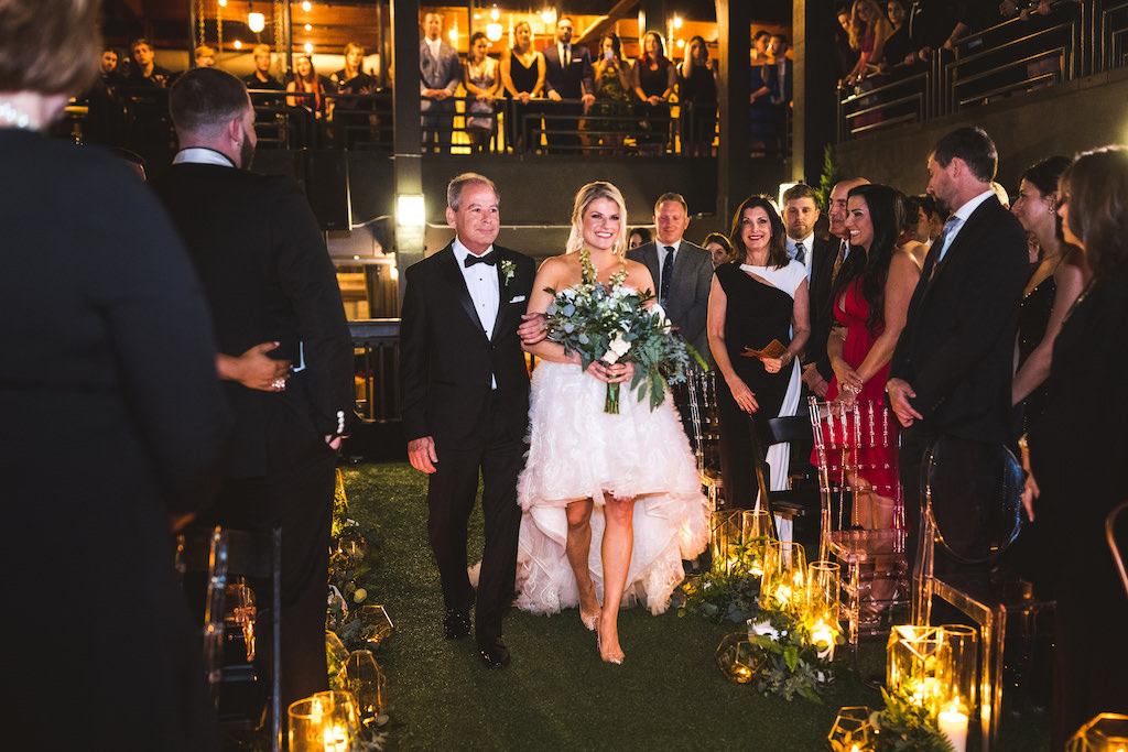 Modern Bride in High Low Ruffled Skirt Ines Di Santo Wedding Dress Holding Greenery and White Floral Bouquet with Father Walking Down the Wedding Ceremony Aisle, Romantic Candles, New Years Eve Nighttime Rooftop Wedding   St. Petersburg Wedding Venue Station House