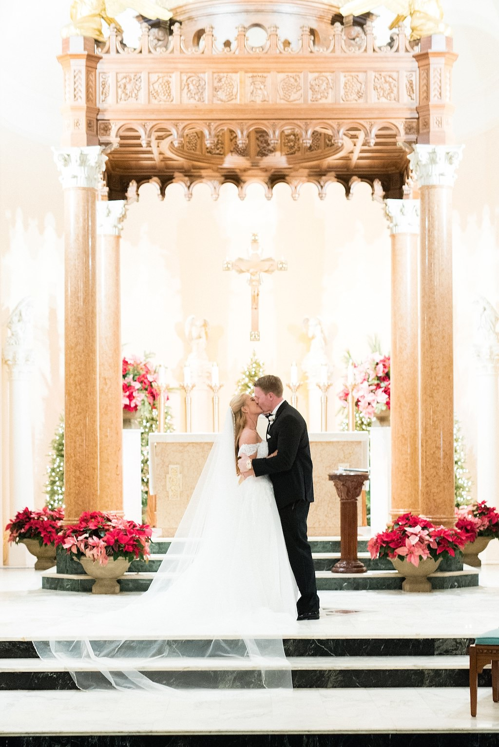 Winter Christmas Traditional Church Wedding Ceremony Bride and Groom Exchanging First Kiss Under Elegant Gold Arch, Bride Wearing Cathedral Veil | St. Petersburg Wedding Venue St. Mary Our Lady of Grace Catholic Church