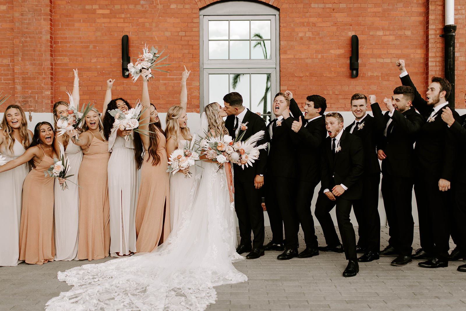 Boho Whimsical Excited Fun Cheering Wedding Party Portrait, Bridesmaids in Mix and Match Neutral, Sandy Blush Dresses with Palm Tree Leaves, Blush Pink Roses Floral Bouquets, Groomsmen in Black Suite, Bride in Lace and Tulle Martina Liana Wedding Dress with Cathedral Length Veil Outside Red Brick Building   Tampa Bay Wedding Planner Coastal Coordinating   Industrial Wedding Venue Armature Works