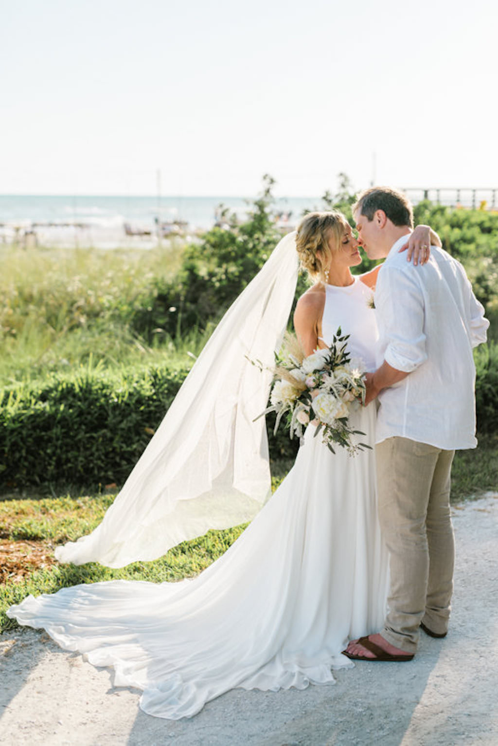 Sarasota Florida Destination Bride and Groom Beachfront Casual Wedding Attire with Bride in White Flowy Dress with Veil Blowing in Wind | Resort at Longboat Key Club