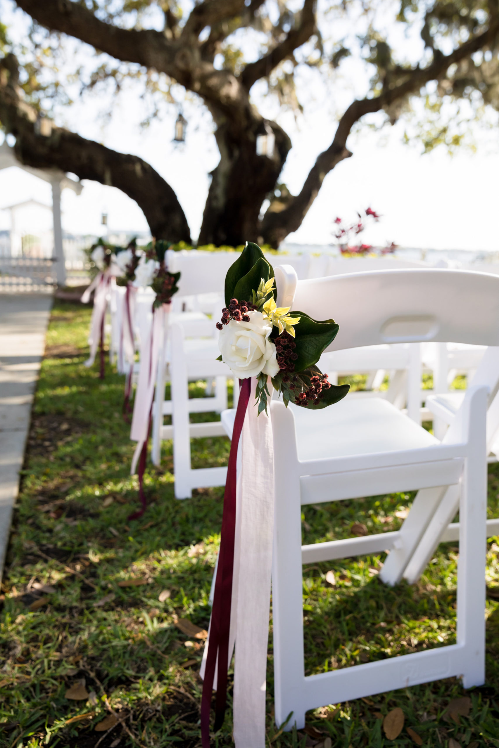 Simple Classic Wedding Ceremony Decor With White Folding Chairs White Rose With Green Leaves And Burgundy Accent Tampa Bay Wedding Planner Coastal Coordinating Marry Me Tampa Bay Local Real