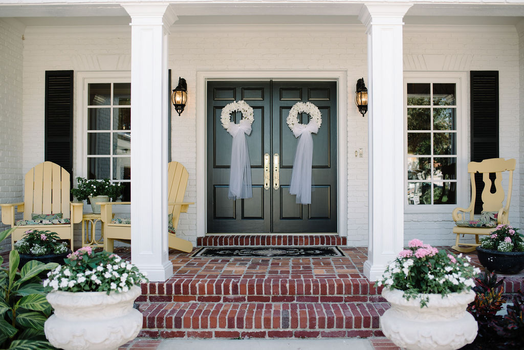 Black Doors with White Floral Wreaths and Tulle Bows Hanging