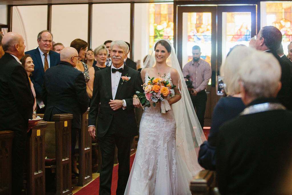 Florida Bride and Father Walking Down Traditional Church Wedding Ceremony Aisle Holding Whimsical Orange, Pink Roses and Greenery Floral Bouquet | Tampa Bay Wedding Hair and Makeup Femme Akoi Beauty Studio | St. Pete Wedding Florist Bruce Wayne Florals