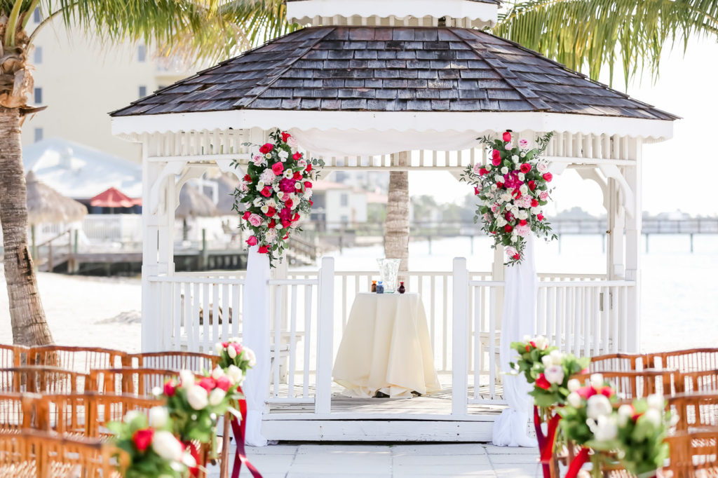Tropical Romantic Wedding Ceremony Decor, White Gazebo with Pink, White, Fuschia and Greenery Floral Arrangements | Tampa Bay Wedding Photographer Lifelong Photography Studios | St. Pete Waterfront Wedding Venue Isla Del Sol Yacht and Country Club