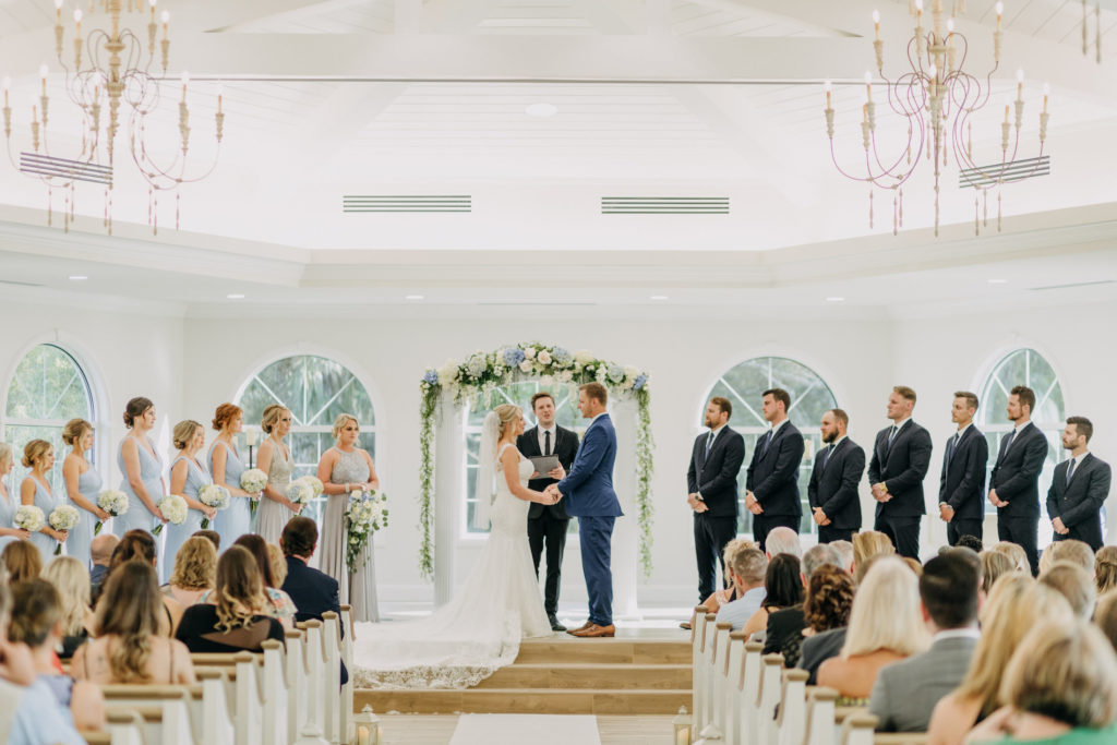 Florida Bride and Groom Exchanging Vows During Traditional Church Wedding Ceremony Portrait Under Greenery and White and Powder Blue Floral Arch | Tampa Wedding Venue Harborside Chapel
