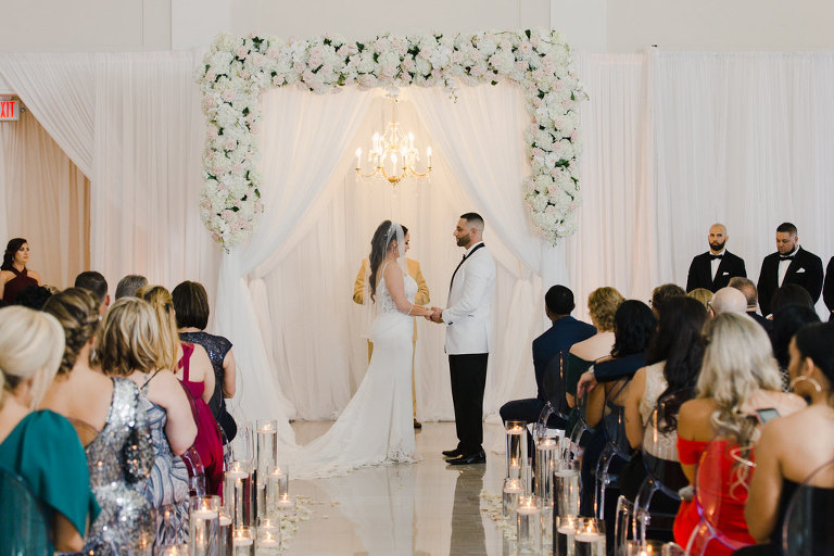 Modern Romantic Bride and Groom Exchanging Vows During Wedding Ceremony, White Draping Backdrop with White and Blush Pink Floral Arrangement Arch and Gold Crystal Hanging Chandelier | Tampa Bay Wedding Venue The Vault | Wedding Florist and Rentals Gabro Event Services