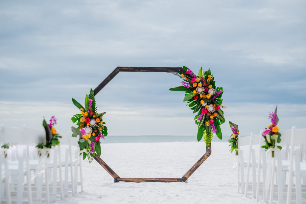 INSTAGRAM Clearwater Beach Waterfront Beachfront Wedding Reception Decor, Tropical Floral Arrangements, King Proteas, Palm Fronds, Monstera Palm Leaves, Orange, Pink, Purple and Yellow Floral Arrangements on Geometric Octagonal Ceremony Arch