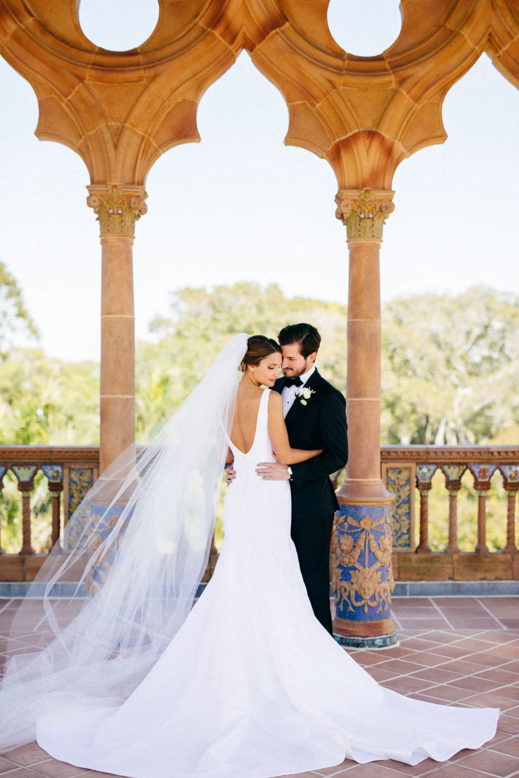 Bride in Classic Silhouette Open Back Wedding Dress and Full Length Veil and Groom First Look Wedding Portrait at Sarasota Waterfront Wedding Venue Ca d'Zan at The Ringling Museum