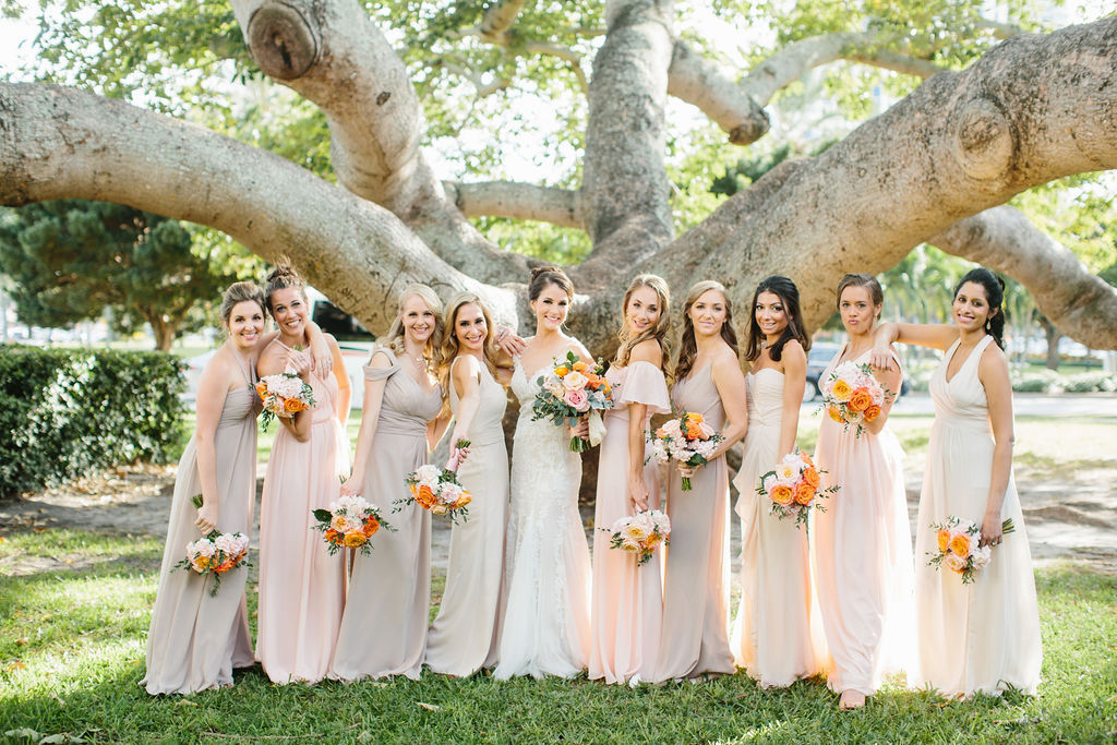 Romantic Bridal Party Portrait, Bridesmaids Wearing Mix and Match Blush Pink, Neutral and Champagne Dresses Holding Whimsical Orange and Pink Roses with Greenery Floral Bouquets, Bride in Lace and Illusion Neckline Fit and Flare Watters Wedding Dress | St. Petersburg Wedding Hair and Makeup Femme Akoi Beauty Studio | Tampa Bay Wedding Florist Bruce Wayne Florals