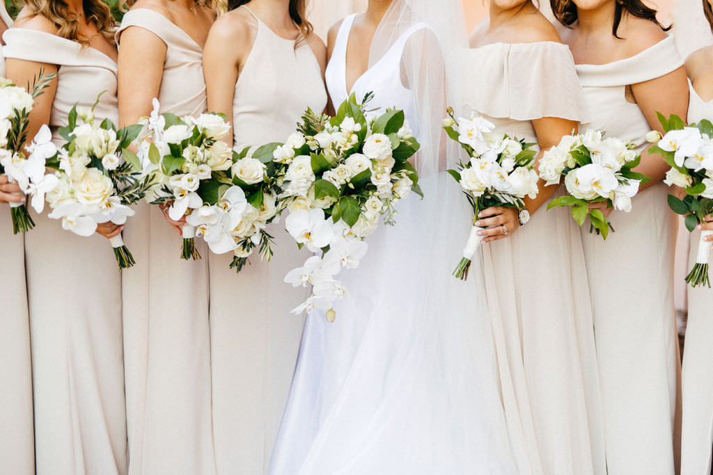 Classic Bride Holding White Orchids and Roses with Greenery Floral Bouquet and Bridesmaids in Neutral Cream Mix and Match Dresses Bridal Party Portrait