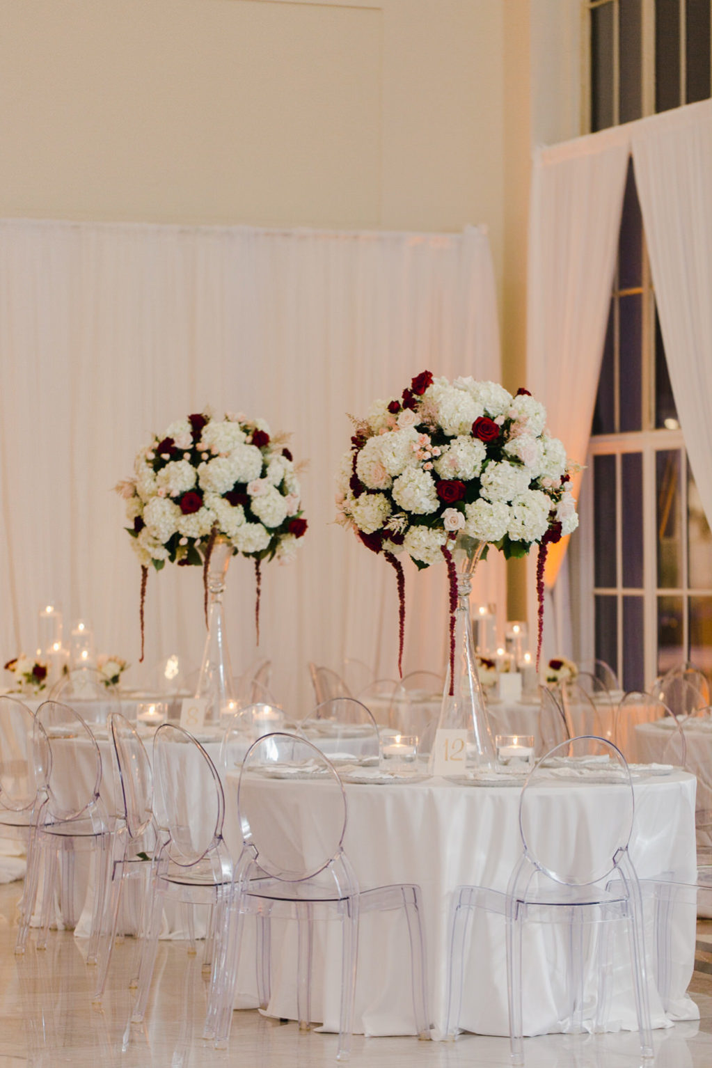 Elegant Wedding Reception Decor, Round Tables with White Tablecloths, Acrylic Ghost Chairs, Tall Glass Vase with White and Blush Pink Hydrangeas with Dark Red Hanging Amaranthus | Tampa Bay Wedding Venue The Vault | Wedding Florist and Rentals Gabro Event Services