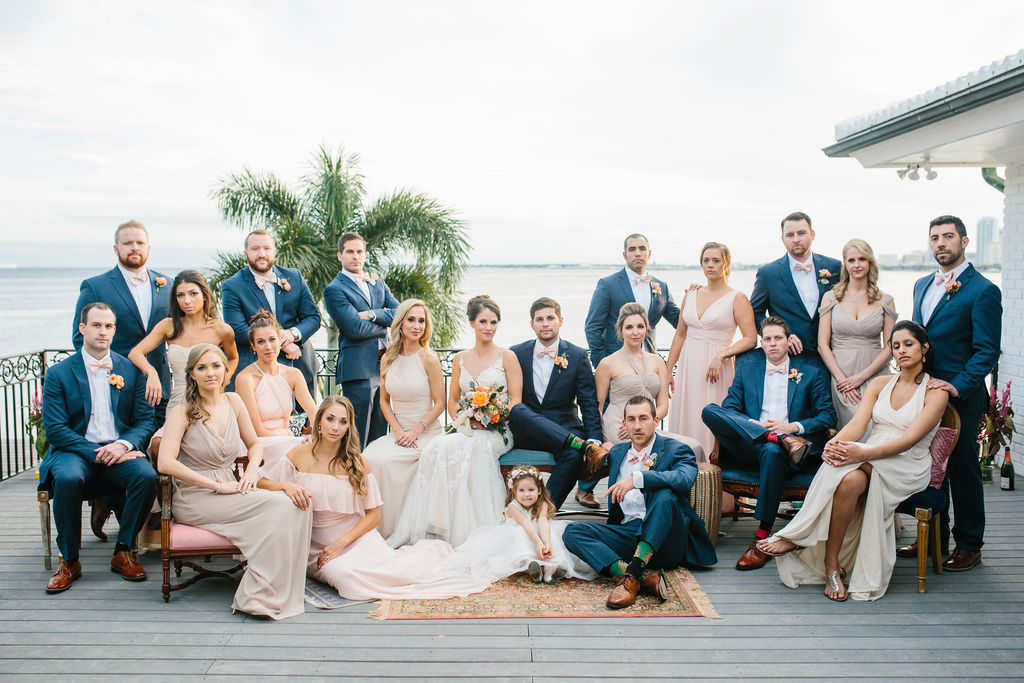 Tampa Bay Waterfront Wedding Party Portrait, Bridesmaids in Mix and Match Blush Pink, Neutral and Champagne Dresses, Groomsmen in Blue Suits with Pink Bowties, Bride in Lace and Illusion Neckline Watters Wedding Dress Holding Whimsical Orange and Pink Roses with Greenery Floral Bouquet | St. Petersburg Wedding Hair and Makeup Femme Akoi Beauty Studio