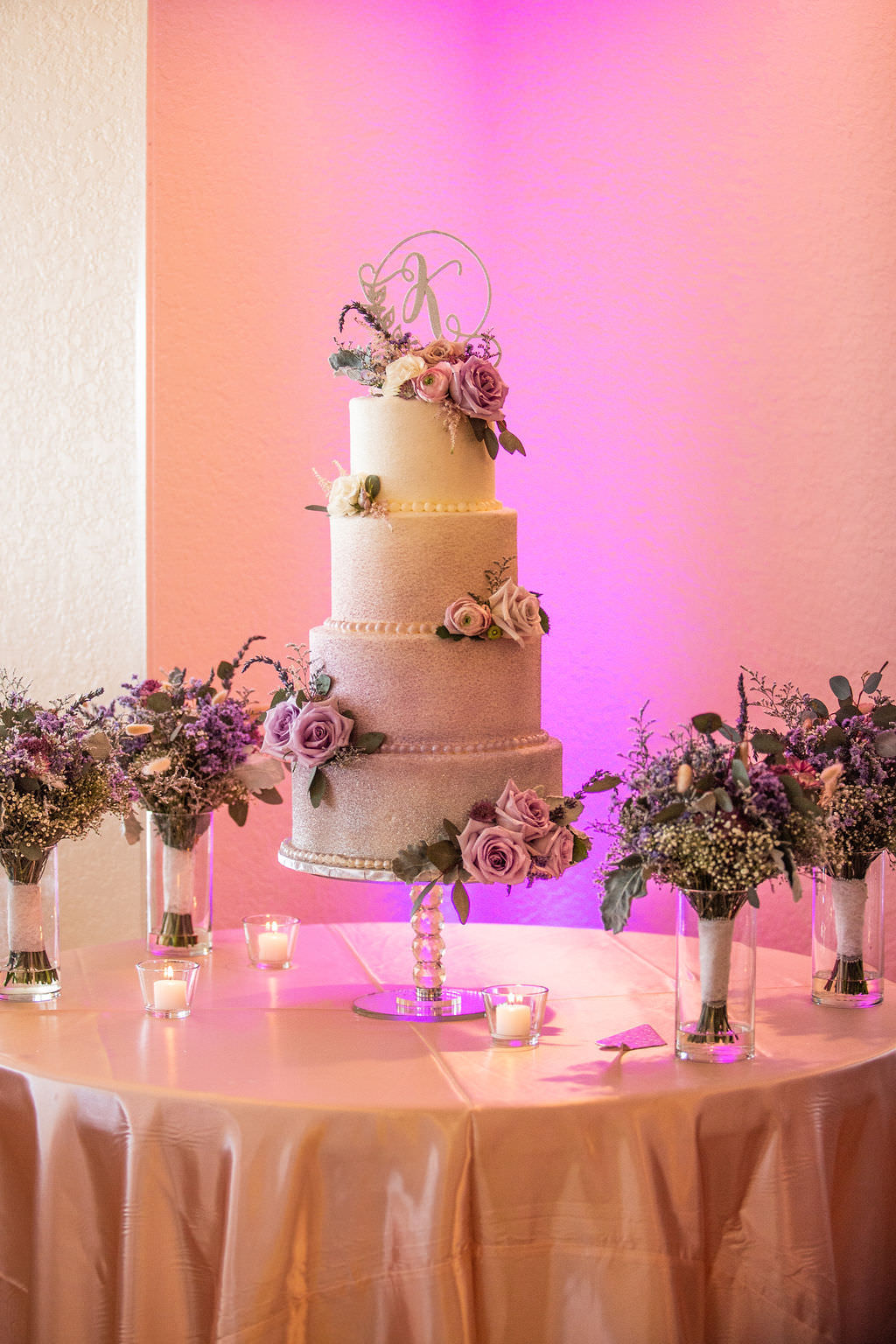 Elegant and Simple Four Tier White with Glitter Embellishments Wedding Cake, Lilac and Blush Pink Roses, Custom Laser Cut Monogram Topper, Pink Uplighting | Tampa Bay Wedding Cake Bakery The Artistic Whisk