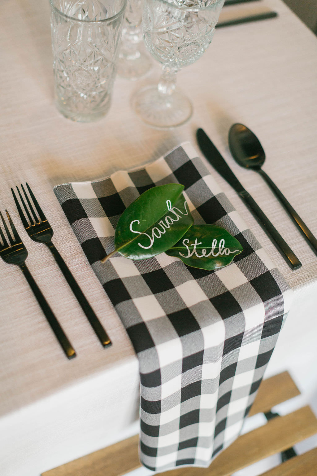 Magnolia Leaf Name Card with White Script Writing | Southern Inspired Magnolia Market Bridal Shower with Buffalo Plaid Linen Accents and Rustic Decor | Bruce Wayne Florals | A Chair Affair | Over the Top Rental Linens | Parties A'La Carte Wedding and Event Planner