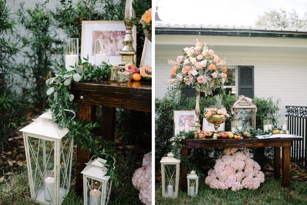 Romantic Whimsical Wedding Reception Decor, Rustic Wooden Table with Eucalyptus Garland, Fruits, Candles, Tall Gold Candlestick with Blush Pink, Orange Roses, Dusty Miller and Greenery Floral Arrangement, White Lanterns, Blush Pink Hydrangeas | Tampa Bay Wedding Florist Bruce Wayne Florals | St. Petersburg Wedding Rentals Gabro Event Services