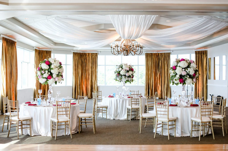 Tropical Romantic Ballroom Wedding Reception Decor, Round Tables with White Tablecloths, Maroon Linens, Gold Chiavari Chairs, Tall White Hydrangeas, Pink and Blush Roses with Greenery Floral Centerpieces, White Ceiling Draping, Gold Curtains | Tampa Bay Wedding Photographer Lifelong Photography Studios | St. Pete Waterfront Wedding Venue Isla Del Sol Yacht and Country Club | Wedding Rentals a Chair Affair, Over the Top Linens