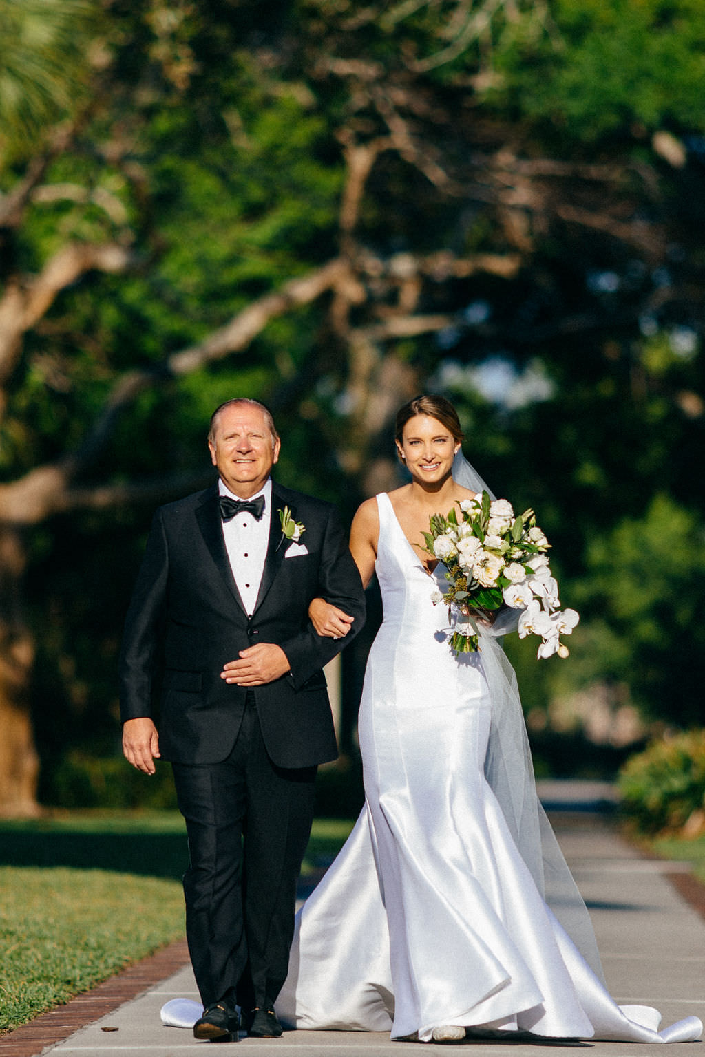 Bride in Classic Silhouette V Neckline Wedding Dress Holding White Orchids and Greenery Floral Bouquet Walking Down the Wedding Ceremony Aisle with Father   Tampa Bay Wedding Planner NK Productions   Wedding Hair and Makeup Femme Akoi Beauty Studio