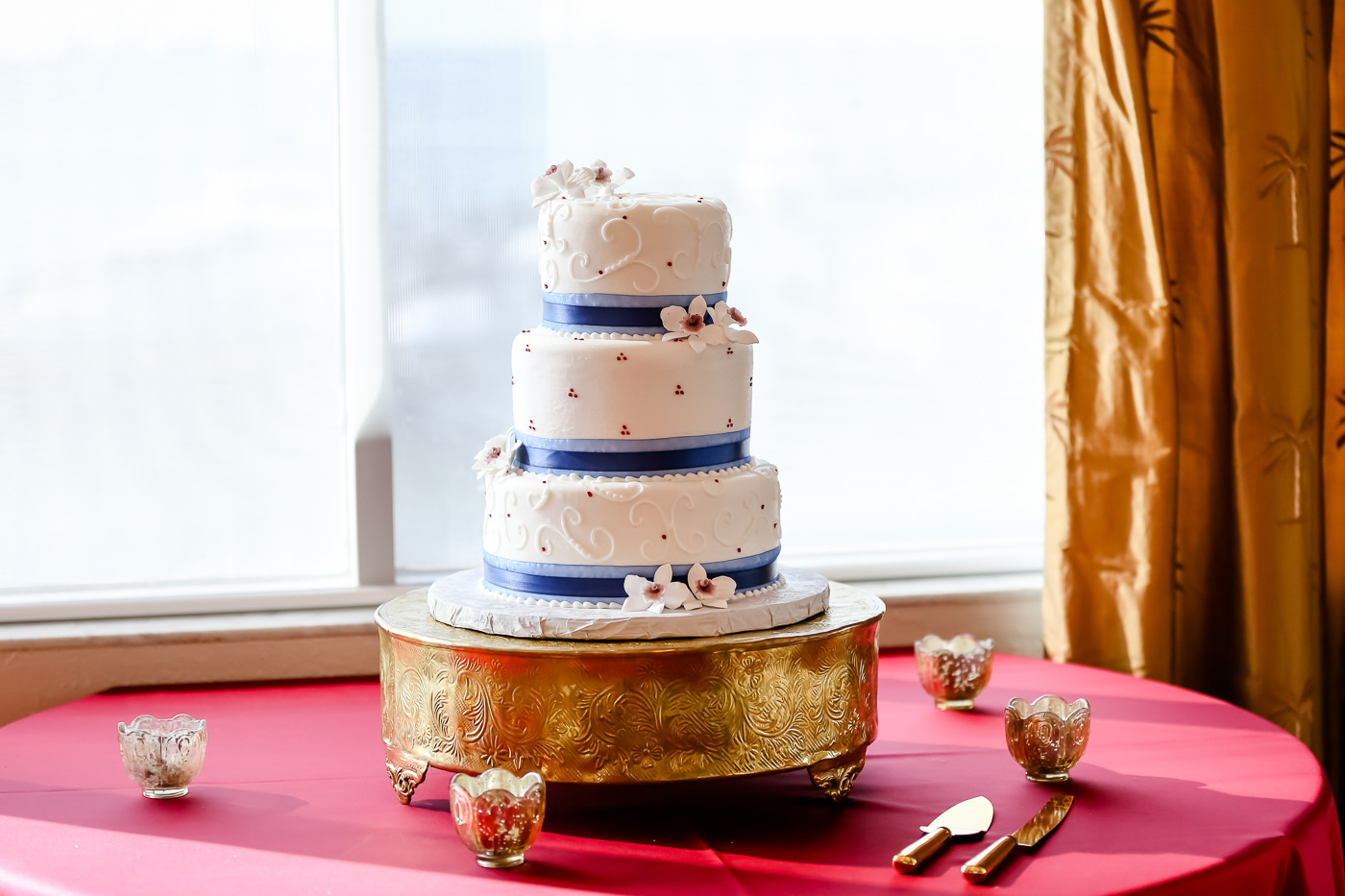 Three Tier White Classic Wedding Cake With Swirls Red Accents Blue Ribbons And Sugar Flowers On Gold Cake Stand And Table With Maroon Linen Tampa Bay Wedding Photographer Lifelong Photography Studios