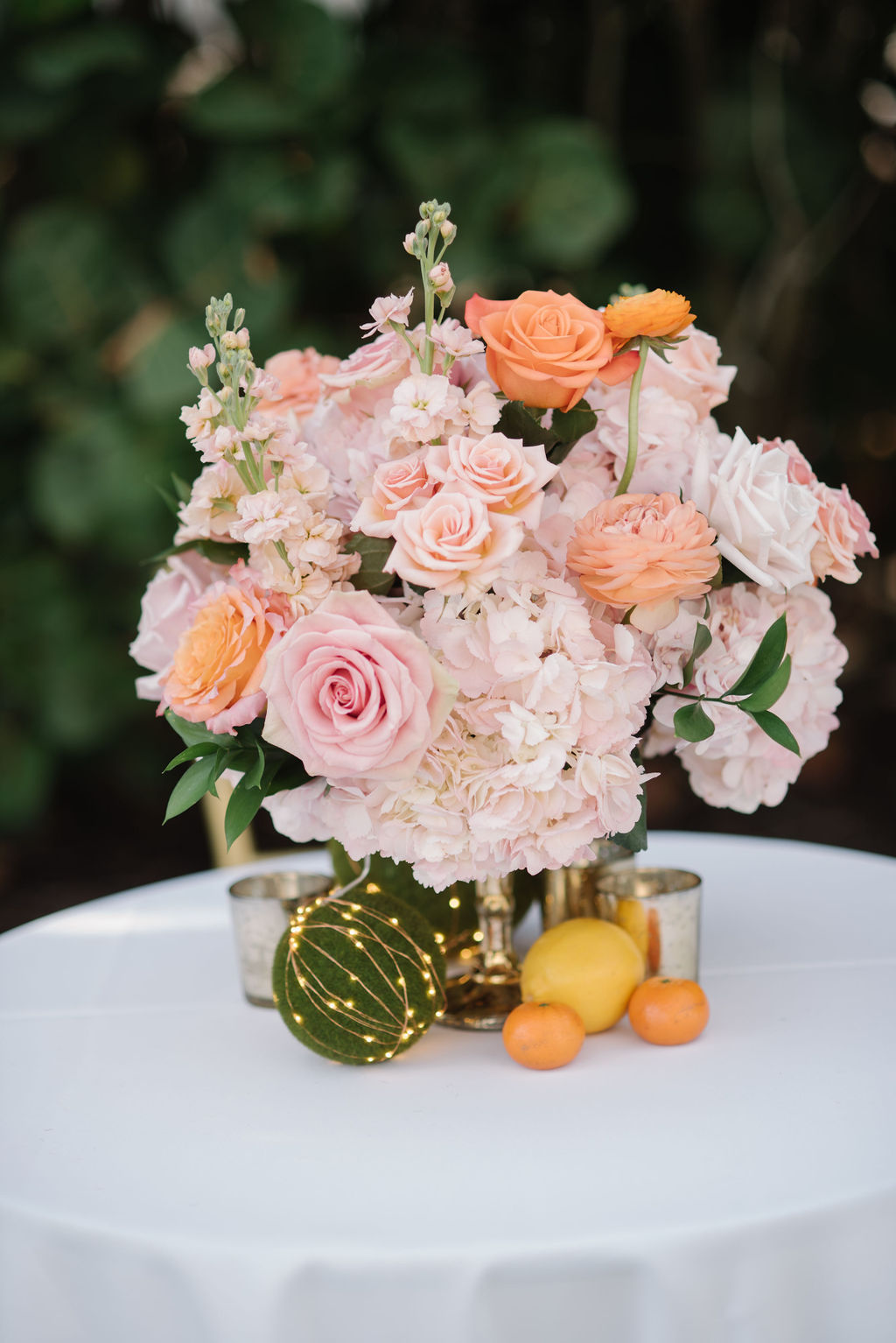 Romantic Whimsical Wedding Reception Decor, Blush Pink Hydrangeas, Orange and Pink Roses in Gold Vase Low Floral Centerpiece with Oranges and Lemon Fruits | Tampa Bay Wedding Florist Bruce Wayne Florals