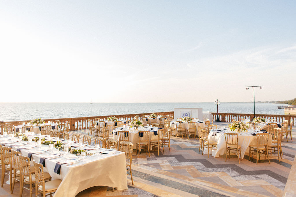 Classic Elegant Waterfront Wedding Reception Decor, Long Feasting Tables and Round Tables with White Tablecloths, Navy Blue Linens, Gold Chairs and Low Floral Centerpieces   Sarasota Historic Wedding Venue Ca d'Zan at The Ringling Museum   Tampa Bay Wedding Planner NK Productions
