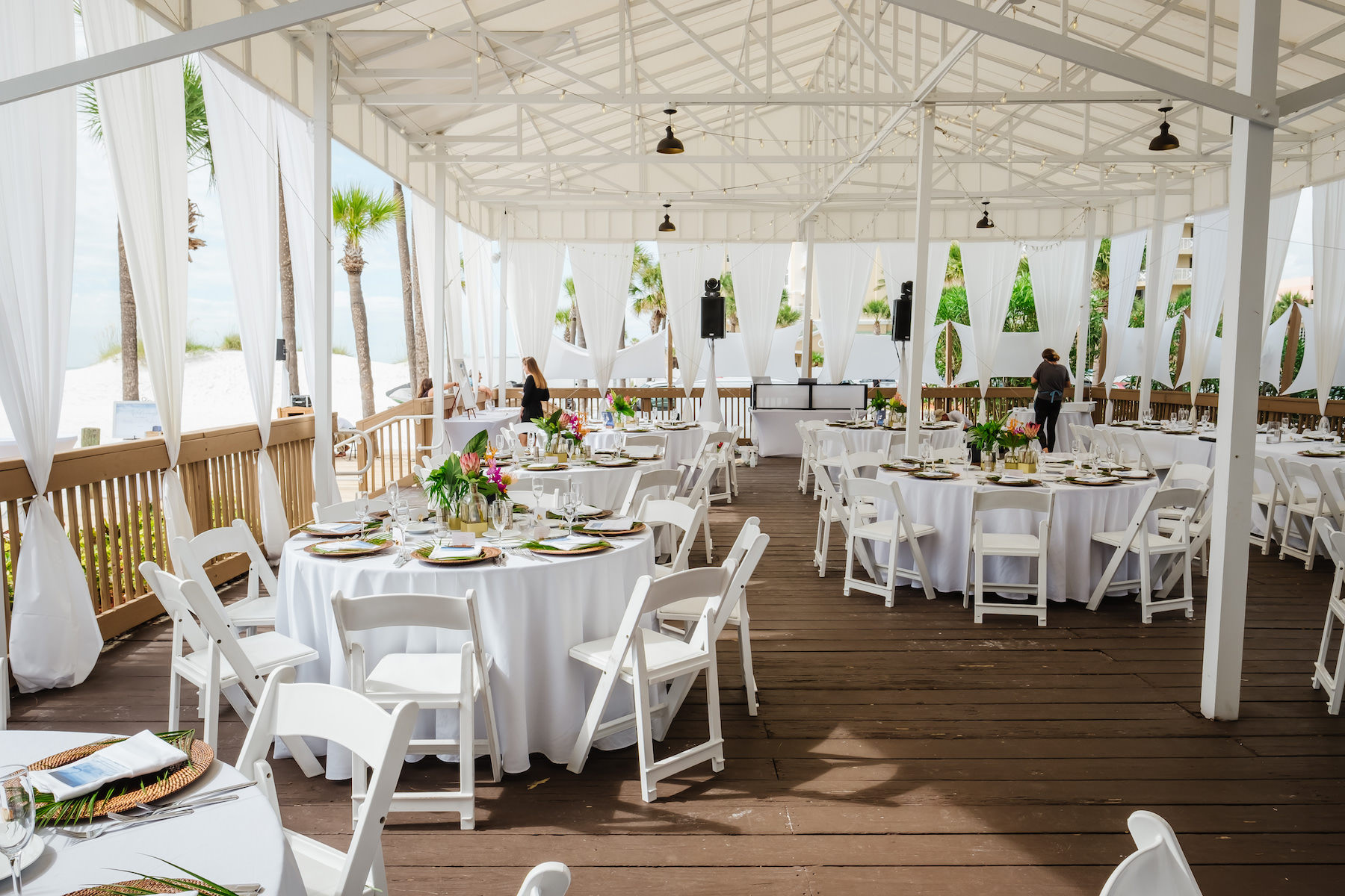 Tropical Wedding Reception Decor Round Tables With White Linens White Folding Chairs And Colorful Floral Centerpieces White Draping Outdoor Florida Beach Hotel Wedding Venue Hilton Clearwater Beach Resort And Spa