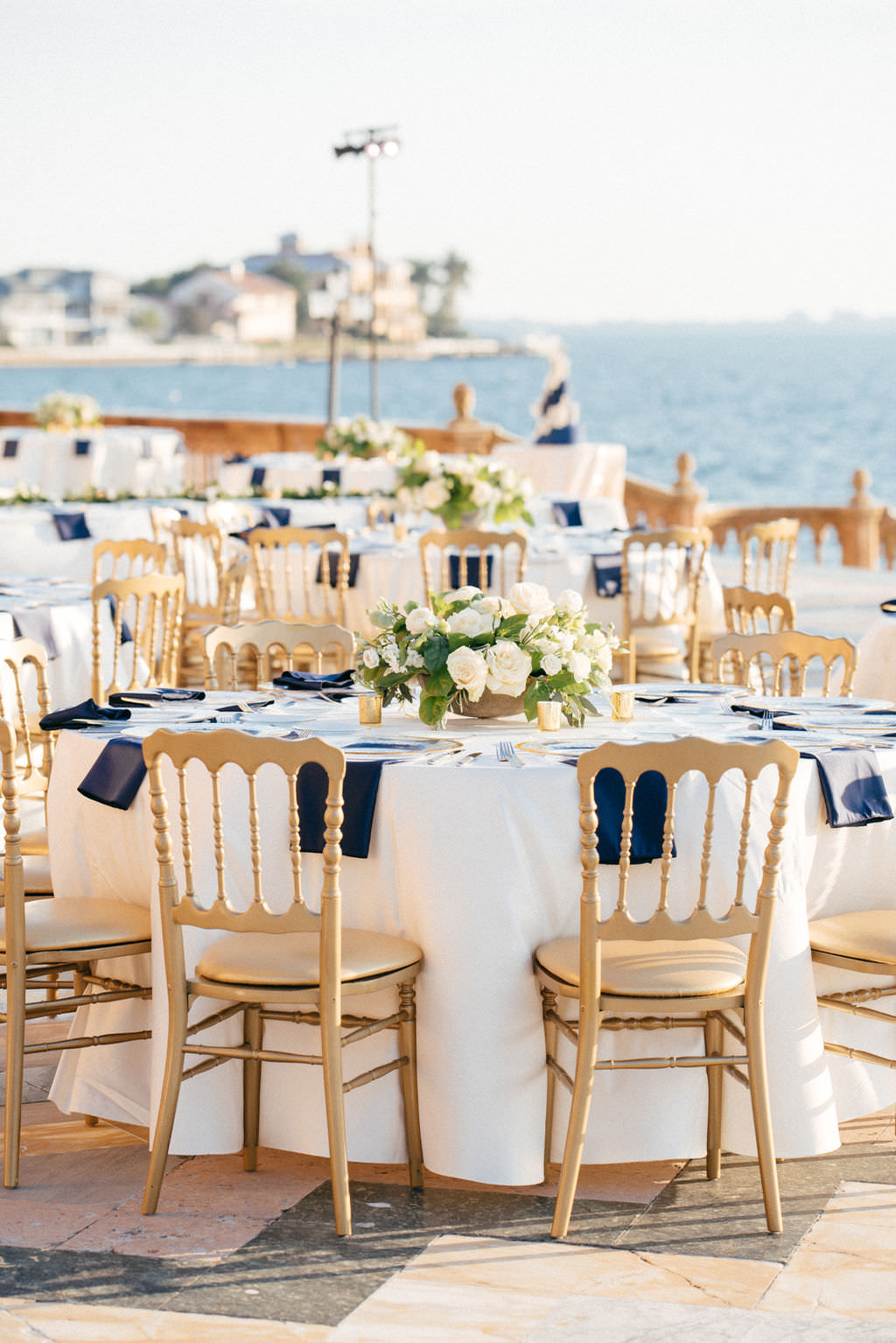 Classic Elegant Wedding Reception Decor, Round Tables with White Tablecloths and Navy Blue Linens, Gold Chairs, White and Greenery Floral Low Centerpieces   Sarasota Historic Waterfront Wedding Venue Ca d'Zan at The Ringling Museum   Tampa Bay Wedding Planner NK Productions