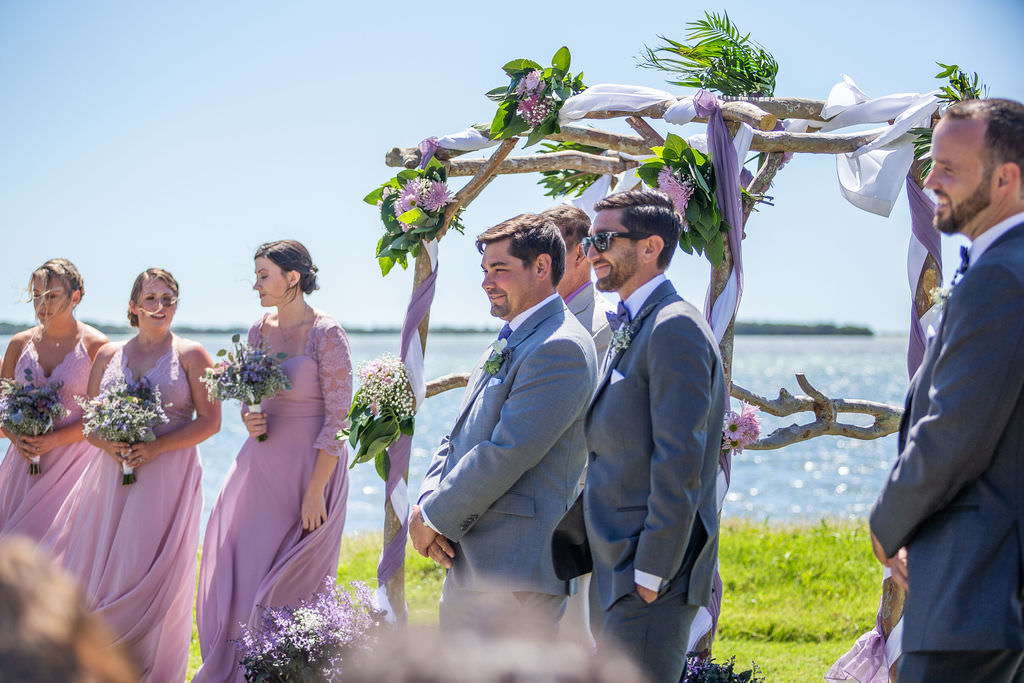 Easter Spring Wedding Theme, Tampa Bay Groom and Wedding Party at Waterfront Ceremony, Birchwood Arch with Purple and White Draping, Greenery and Lilac Floral Arrangements