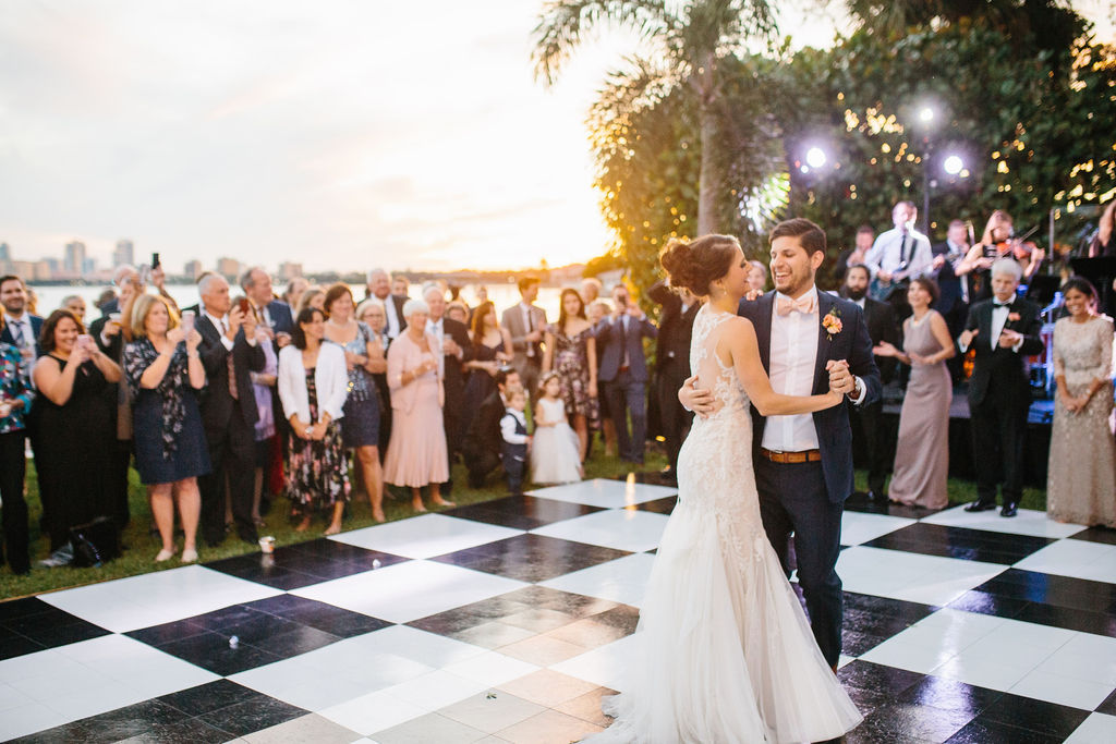 Romantic Bride and Groom Sunset First Dance Outdoor Waterfront Wedding Portrait on Black and White Checkered Dance Floor | St. Petersburg Wedding Hair and Makeup Femme Akoi Beauty Studio | Wedding Dance Floor Rentals Gabro Event Services